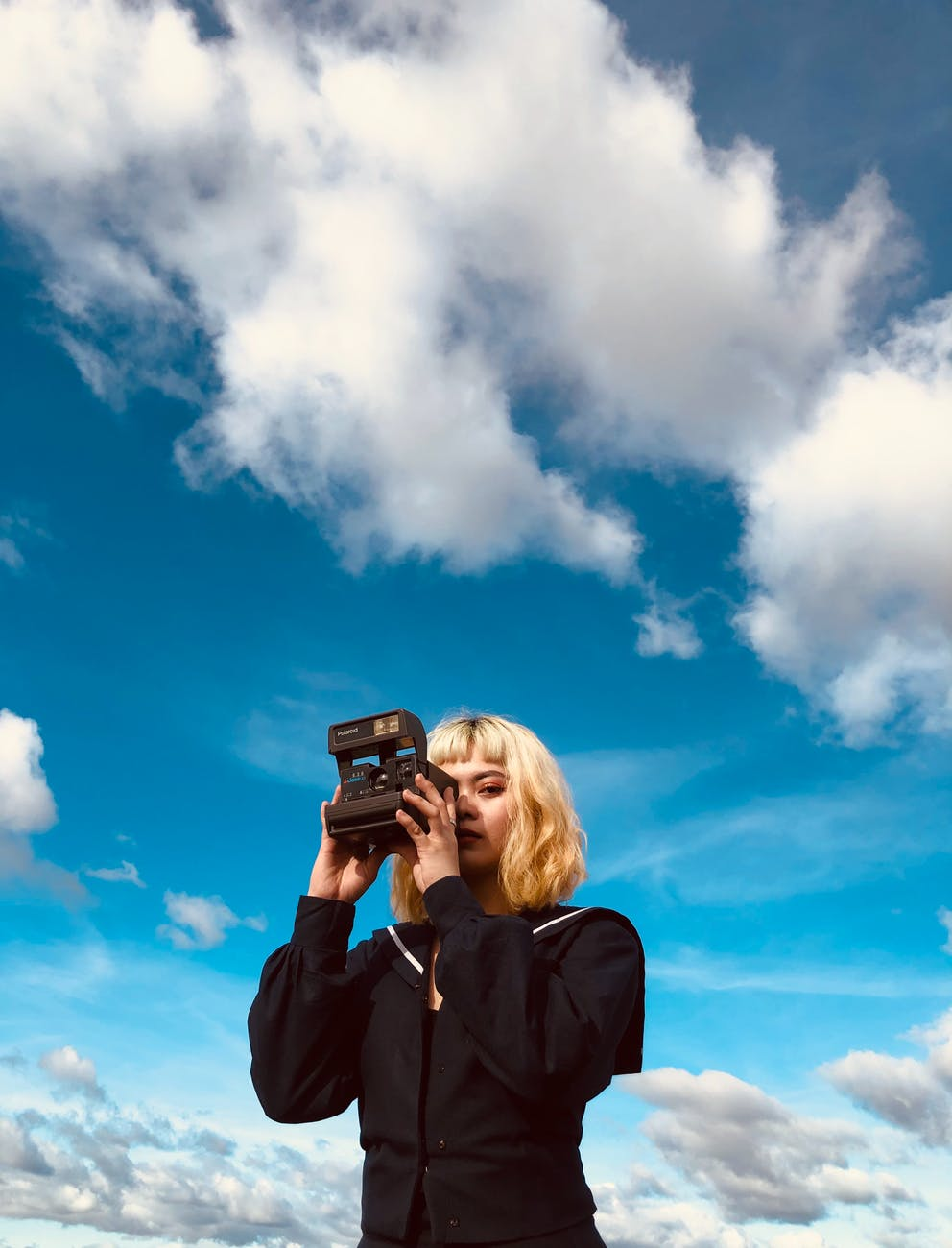 female with instant camera against blue sky